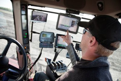 A farmer in a tractor using computer equipment.